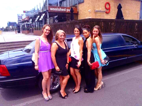 Steph and friends posing for the camera in front of a chauffeured stretch limousine